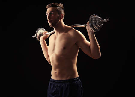 Sporty man doing exercises with barbell on black background Stok Fotoğraf