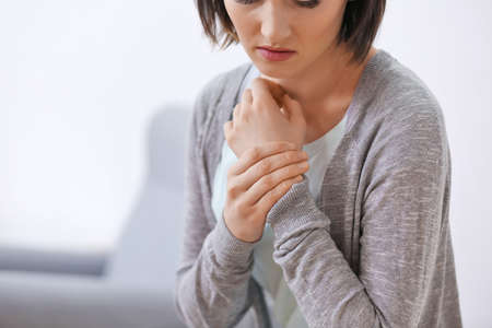 Young woman suffering from pain in wrist, close up Stock Photo
