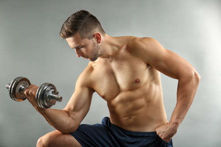 Sporty man doing exercises with dumbbell on light background Stock Photo
