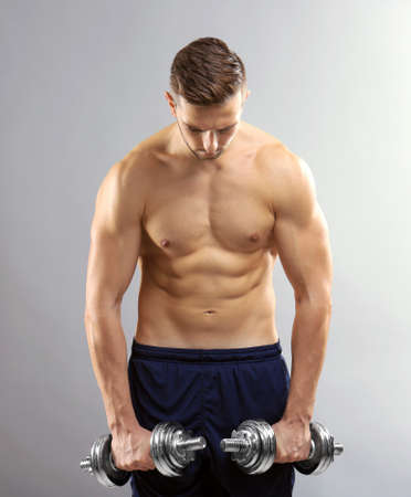 Sporty man doing exercises with dumbbells on light background Stock fotó