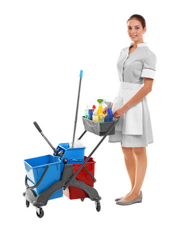 Hotel female chambermaid with cleaning supplies on white background Stock Photo