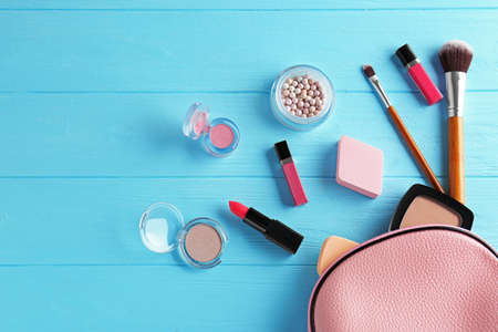 Cosmetic bag and makeup products on wooden   background