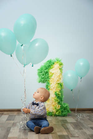 Cute baby boy with birthday decor