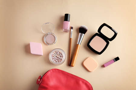 Cosmetic bag and makeup products on color   background Stock Photo