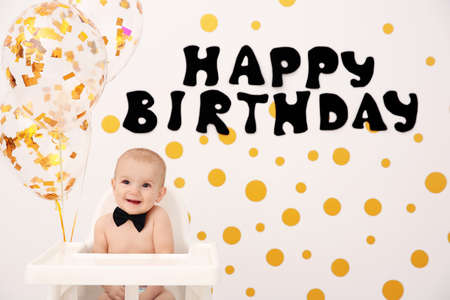 Cute baby boy in high chair on decorated wall background Stock Photo