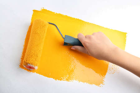 Female hand painting wall with roller