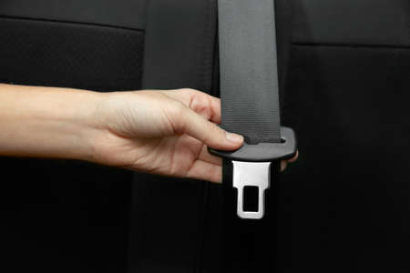Female hand holding seat belt in car