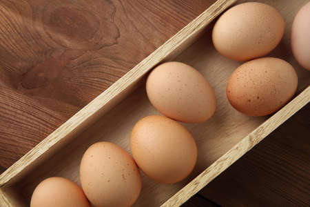 Raw eggs in wooden box, closeup