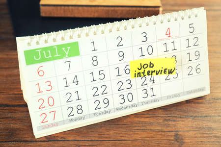 Calendar with job interview reminder on wooden table