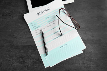 Resume, eyeglasses and pen on grey table