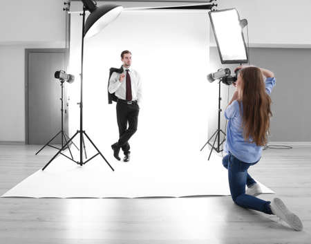 Photographer Taking Picture Of Model In Studio Stock Photo