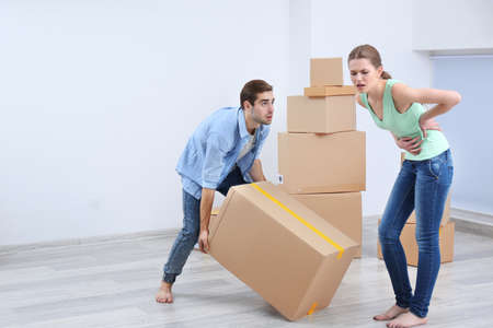 Couple suffering ache moving boxes indoors