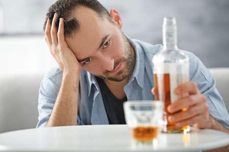 Handsome depressed man drinking whisky at home Banque d'images - 97586834