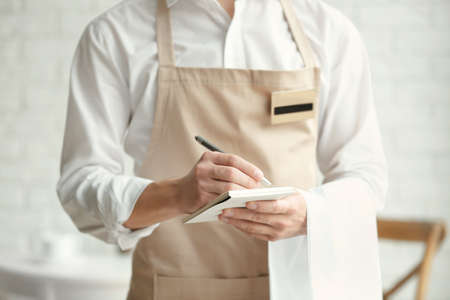 Waiter in beige apron writing down an order in a cafe,close up