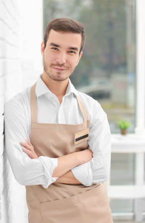 Cute waiter in beige apron on blurred background