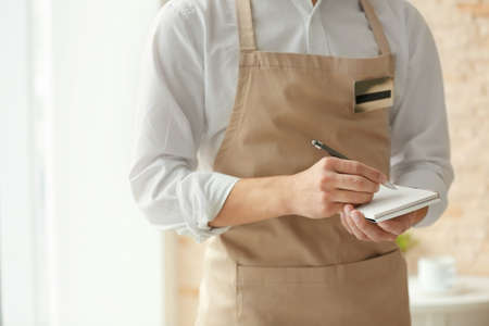 Waiter in beige apron writing down an order in a cafe, close up Stock Photo
