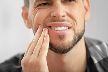 Handsome young man suffering from toothache, closeup