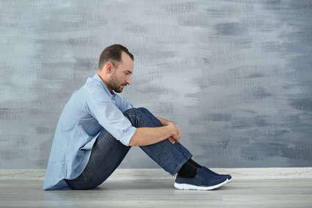 Handsome depressed man sitting on floor near wall