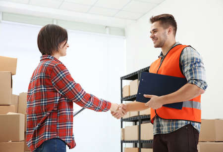 Managers shaking hands at warehouse