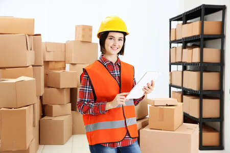 Young woman with tablet checking orders at warehouse