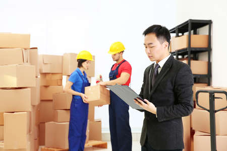 Manager with clipboard standing at logistic company warehouse Stock Photo