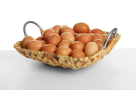 Wicker basket with brown eggs on white background Stock Photo