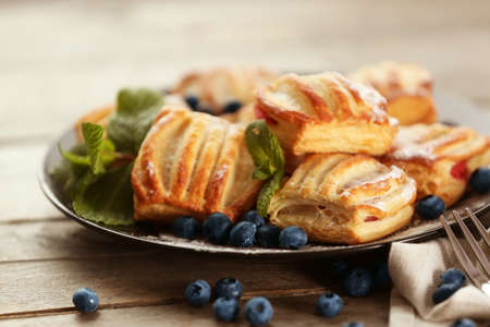 Sweet tasty pastries with bilberries on plate, closeup Stock Photo