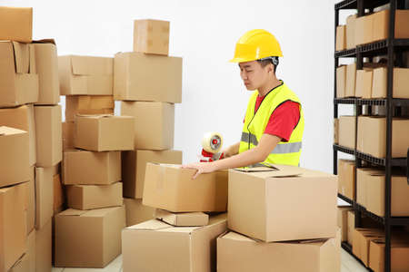 Man packing parcels with sticky tape at warehouse Stock Photo