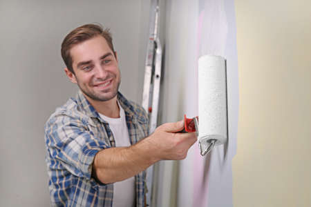 Handsome young man painting wall in room