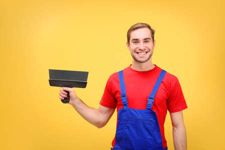 Handsome young worker with putty knife on yellow background