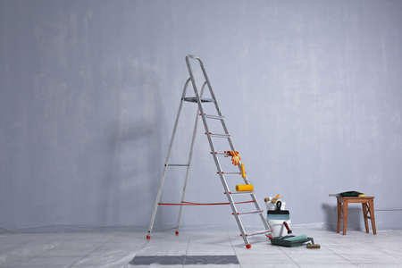 Ladder, paint and tools for making repair in empty room