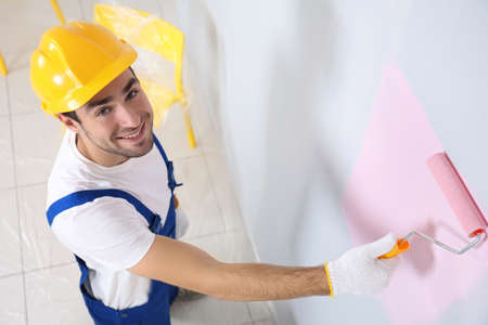 Young worker painting wall in room Stock Photo