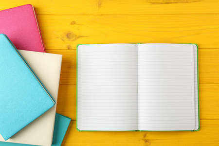 Colorful notebooks on wooden background