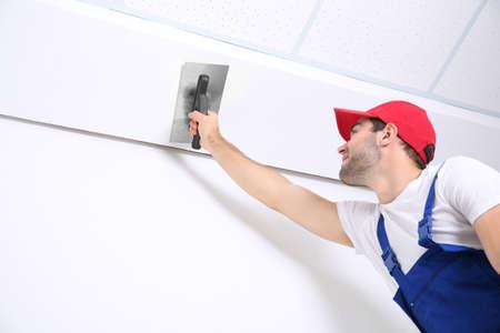 trabajador joven haciendo reparación en la habitación Foto de archivo