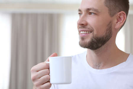 Handsome young man drinking coffee at home, closeup Stock Photo
