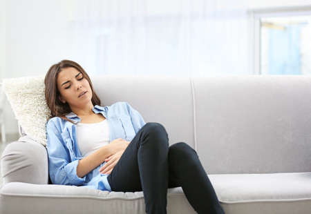 Young woman suffering from abdominal pain at home. Gynecology concept