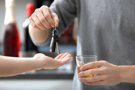 Close up view of drunk man giving car key to woman, on blurred background. Dont drink and drive concept