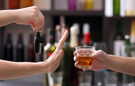 Woman with car key refusing glass of alcoholic beverage, on blurred background. Dont drink and drive concept