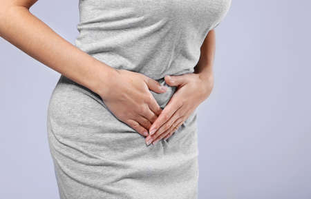 Close up view of woman suffering from abdominal pain on grey background. Gynecology concept Stock Photo