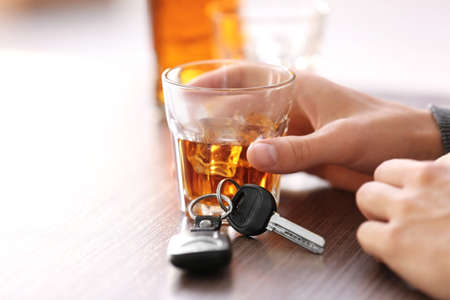 Man sitting in bar with alcoholic beverage and car key, closeup. Dont drink and drive concept