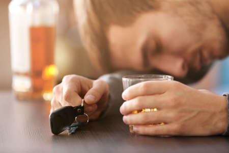 Man sitting in bar with car key and glass of alcoholic beverage, closeup. Dont drink and drive concept Stock Photo