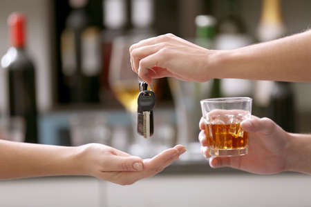 Drunk man giving car key to woman, on blurred background. Dont drink and drive concept