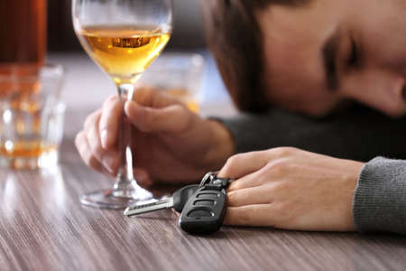 Drunk man sitting at table with car key and glass of alcoholic beverage, closeup. Dont drink and drive concept
