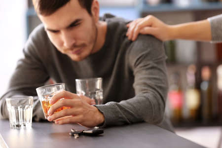 Człowiek z kluczyk samochodowy i napoje alkoholowe w barze. Nie pij i jedź koncepcja