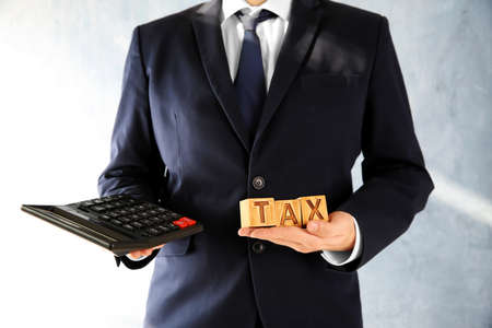 Man holding wooden cubes with word TAX in hand