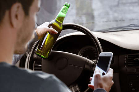 Man holding mobile phone and bottle of beer while driving car, closeup. Don't drink and drive concept
