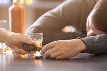 Woman taking car key from drunk man in bar, closeup. Dont drink and drive concept Stock Photo