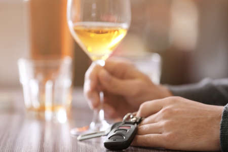 Man sitting at table with car key and glass of alcoholic beverage, closeup. Dont drink and drive concept Stock Photo