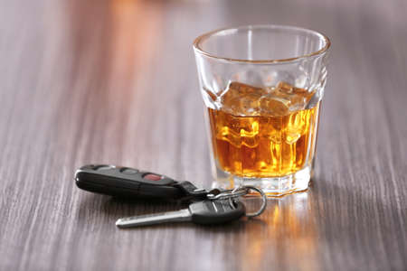 Glass with alcoholic beverage and car key on wooden table. Dont drink and drive concept Stock Photo