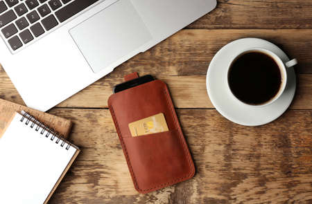 Leather case with mobile phone, laptop, notepads and cup of coffee on wooden table